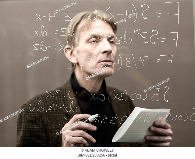 Caucasian teacher looking at formula on glass wall