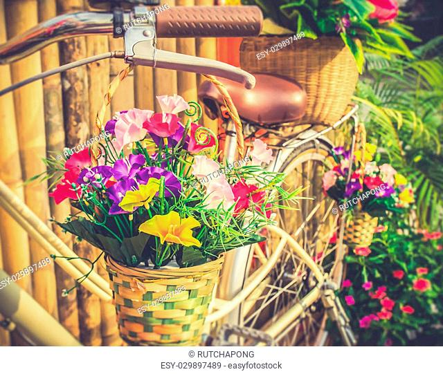 Flowers in basket hanging at bicycle handlebars - with retro filter effect