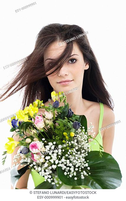 Beauty with a bunch of flowers, hair blowing in her face
