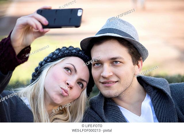 Portrait of couple in love taking selfie with smartphone