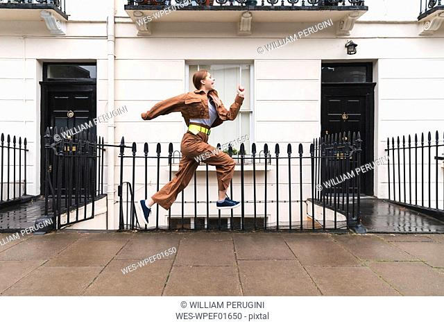 Carefree young woman jumping in front of city houses, London, UK
