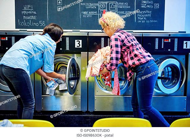 Two women inserting laundry into washing machines at laundrette