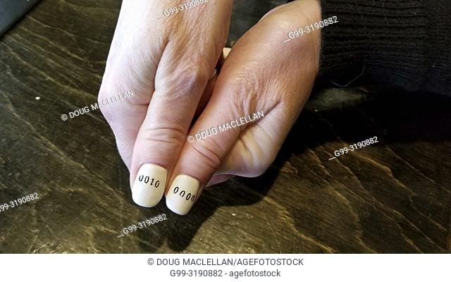 A close up of woman's hands with binary code on her fingernails, Windsor, Ontario