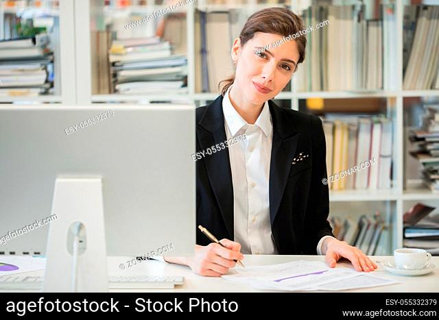 Portrait of business woman working with financial documents and computer