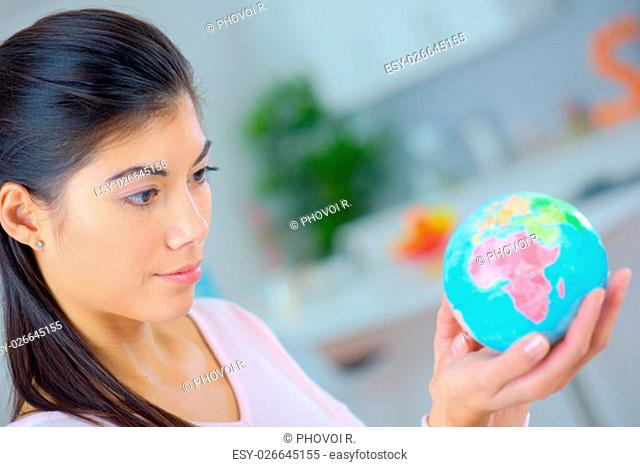 Woman holding a miniature globe