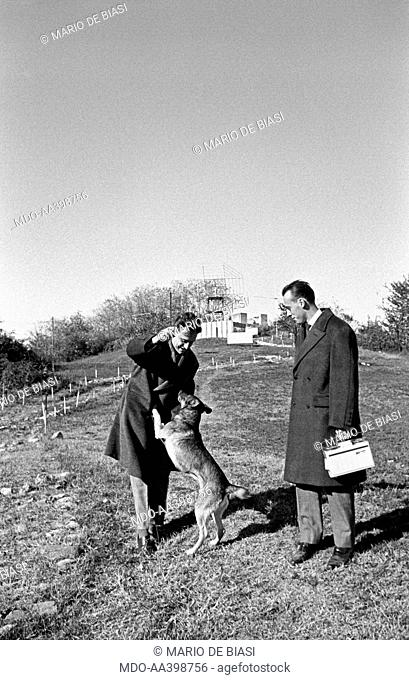 Italian brothers and radio amateurs Achille and Giovanni Battista Judica Cordiglia playing with a dog in front of Bert Tower