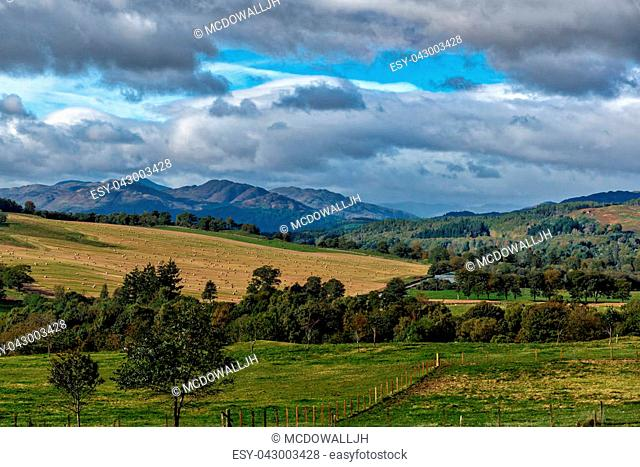 Looking onto the mountains of Perthshire across fields and trees from the area known as Knock in Crieff situated in the highlands of Scotland