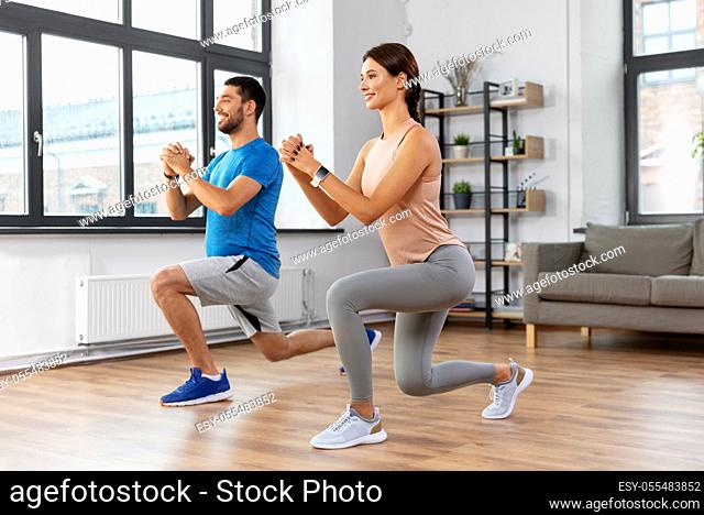 happy couple exercising and doing squats at home