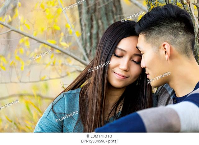 A young Asian couple enjoying a romantic time together and sitting down under a tree in a park in autumn; Edmonton, Alberta, Canada