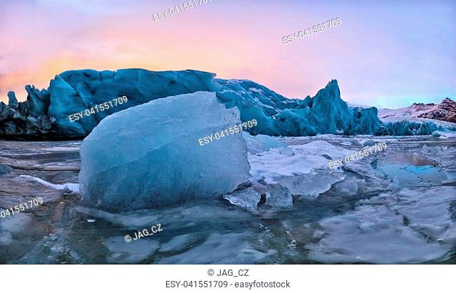 Iceberg lagoon in Fjallsarlon, Iceland. Panoramic view of beautiful sunset light, concept of global warming and ice melting
