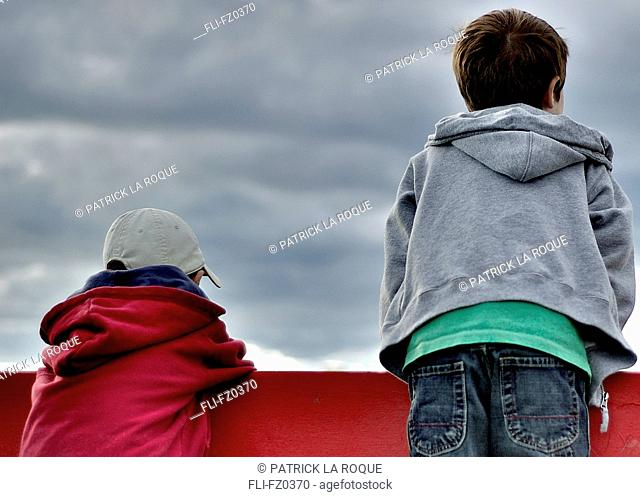 Two boys looking over a red fence, St-Jean sur Richelieu, Quebec