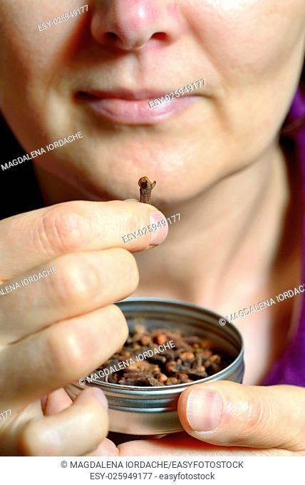 Woman chew dried clove spice for fresh breath