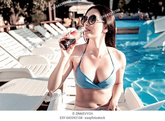 Taste of summer. Waist up shot of a young lady with a laptop on her legs drinking sparkling water while sitting next to a swimming pool and working