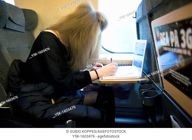 Sundsvall, Sweden. A young, female Swedish student traveling by train from Sundsvall to Stockholm. She is using her laptop computer during the trip and she is...
