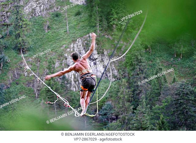 Young outdoor sportsman balancing on slackline over valley in south of Germany, Bavaria, near border to Austria