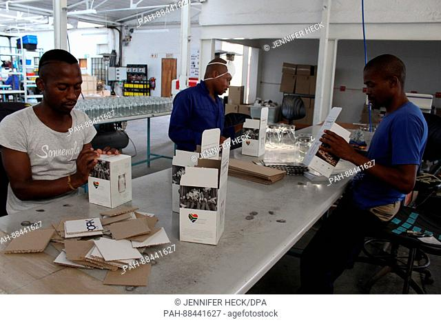 Three employees with the project Consol Solar Jar pack Consol Solar Jar lamps in a factory in Johannesburg, South Africa, 06 February 2017