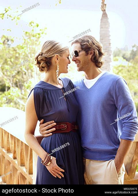 Glamorous Caucasian couple hugging outdoors