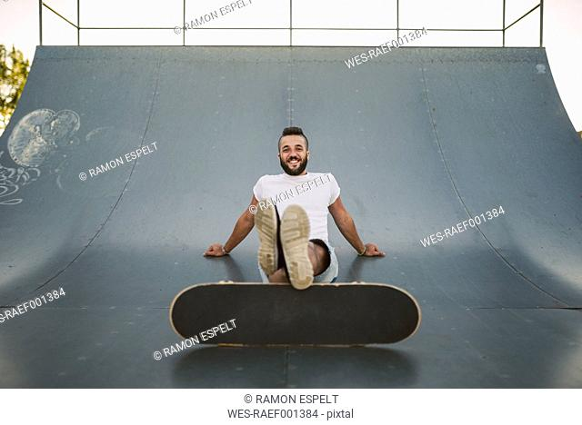 Smiling skateboarder sitting on ramp in a skatepark