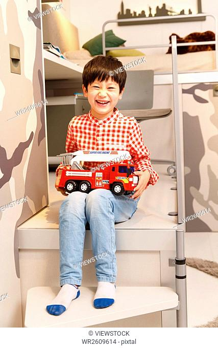 The little boy was holding a toy car in his bedroom