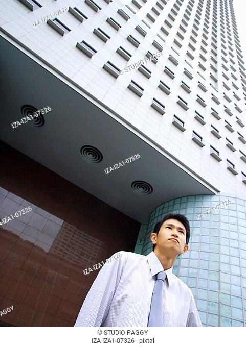 Low angle view of a businessman standing in front of a building