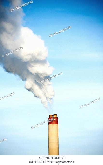 This picture shows an industrial chimney with smoke on a blue sky