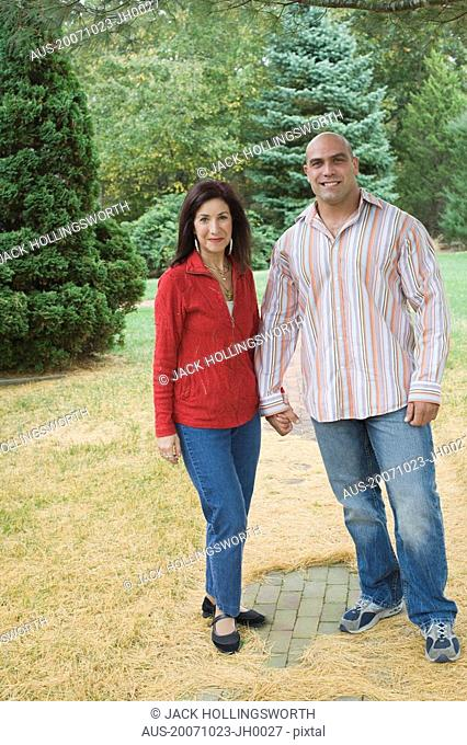 Mid adult man standing with a mature woman in a lawn and smiling