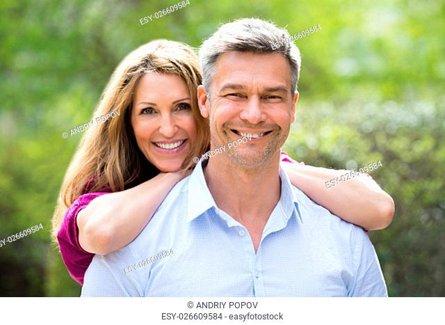 Portrait Of Happy Woman Embracing Her Husband From Behind