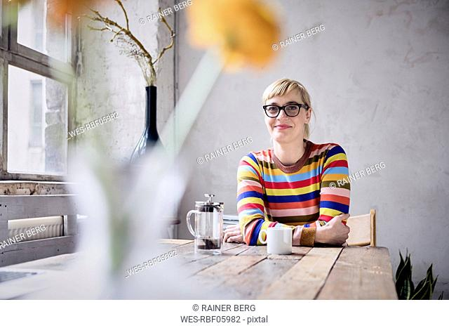 Portrait of smiling woman with cup of coffee in a loft
