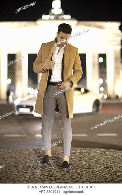 young Afghan man looking down, in front of Brandenburg gate, at street at night, in Berlin, Germany