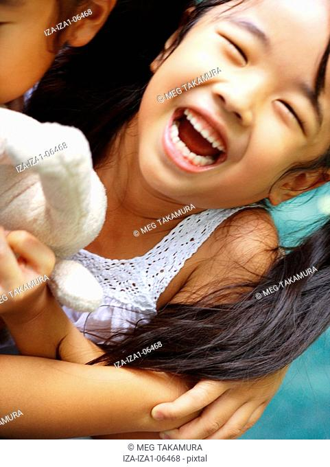 Close-up of two girls playing with a stuffed toy