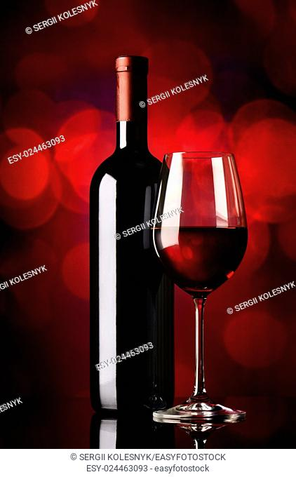 Bottle and glass with red wine on red background