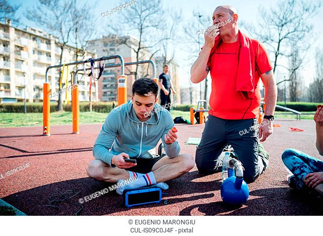 Calisthenics class at outdoor gym, men sitting looking at smartphone and eating fruit