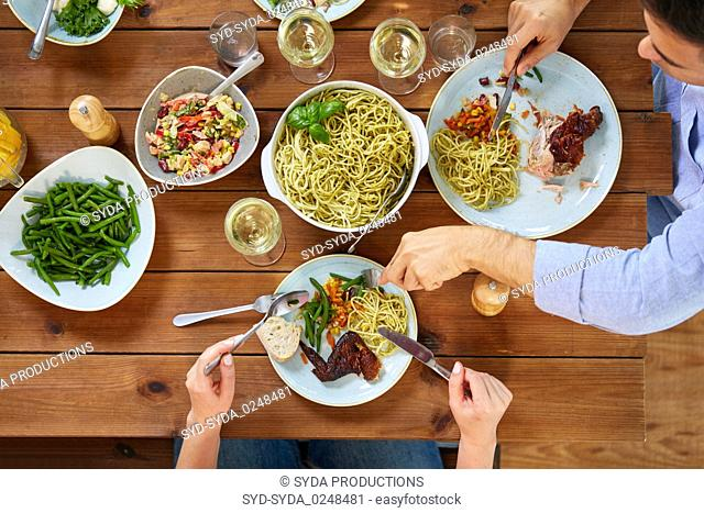 couple at table with food eating pasta and chicken