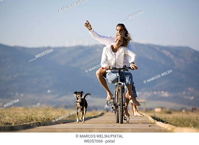 Couple Ridding a Bike With Their Dog