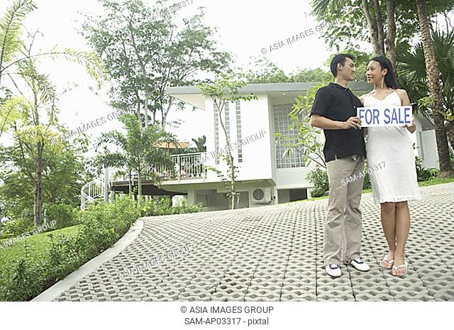 Couple on driveway holding for sale sign