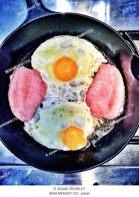 Overhead view of ham and eggs frying in pan