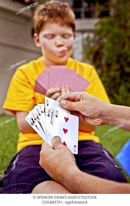 A ten-year-old Caucasian red-headed boy evaluates his hand as he plays cards outdoors in Laguna Niguel, CA  Note partner's cards in foreground