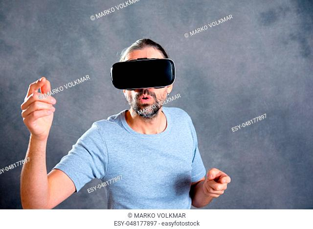 young man using virtual reality glasses and looking surprised