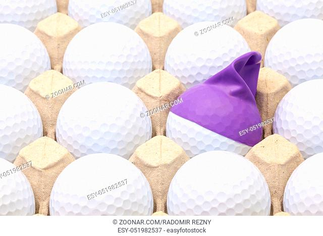 White golf balls in the box for eggs. Golf ball with funny cap.Funny golf concept