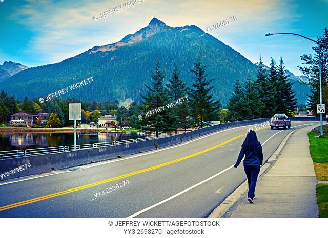 Pedestrian and Mount Verstovia in the distance near downtown Sitka, Alaska, USA