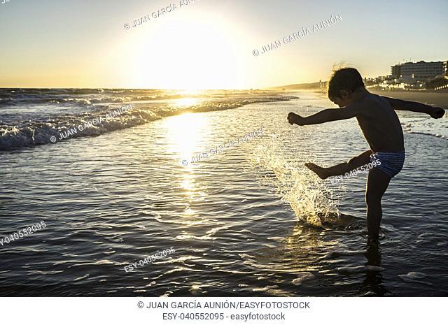 Baby boy playing makes splashes at sunset. Spanish southwest beach. He is kicking the waves