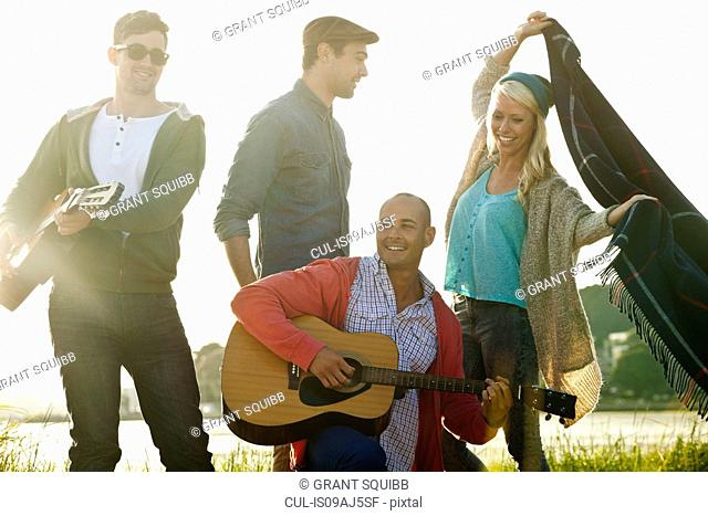 Four adult friends with acoustic guitar and picnic blanket on Bournemouth beach, Dorset, UK