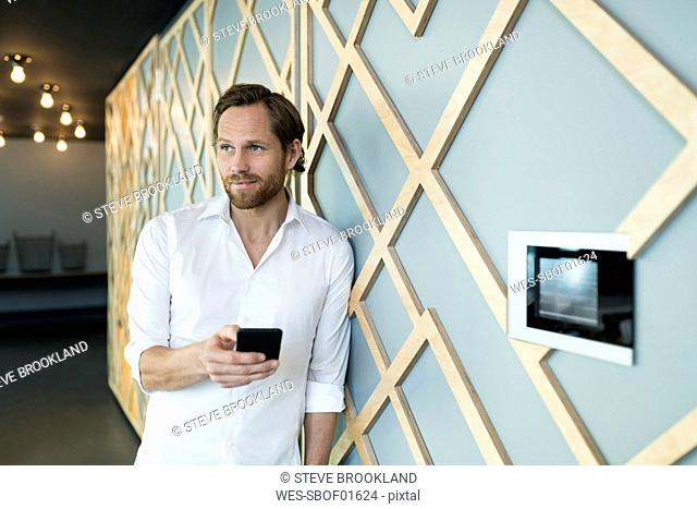 Smiling casual business man leaning onto wall in lounge area holding smartphone
