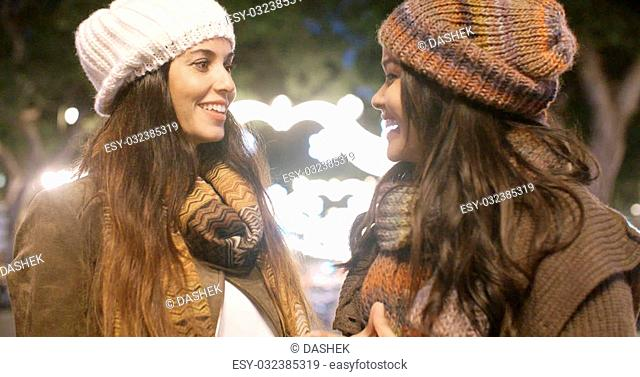 Two young women in trendy winter outfits enjoying a night on the town standing chatting and laughing in a brightly lit urban square