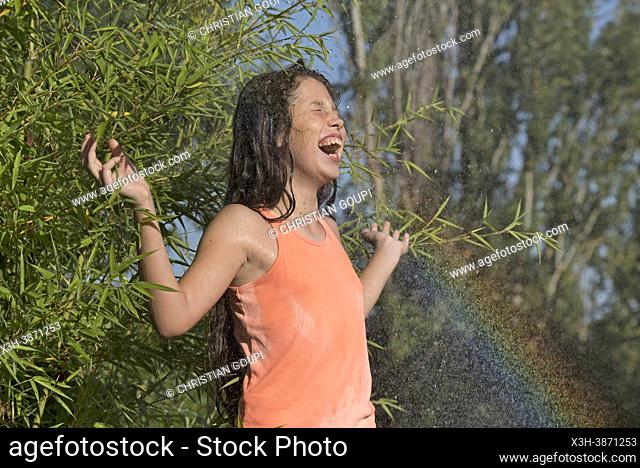 Young girl in denim shorts and pink-orange tank top in the rain of a watering jet creating a rainbow, France