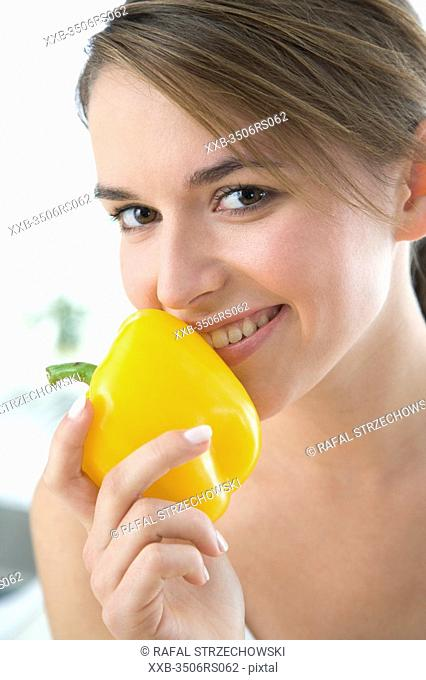young woman smelling yellow paprika