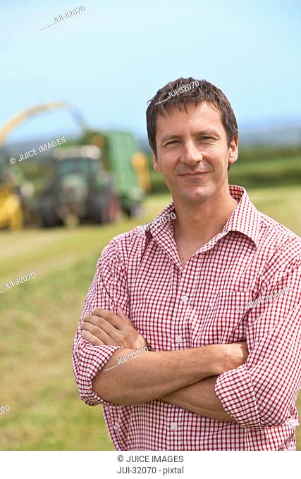Portrait of smiling farmer standing in field with arms crossed