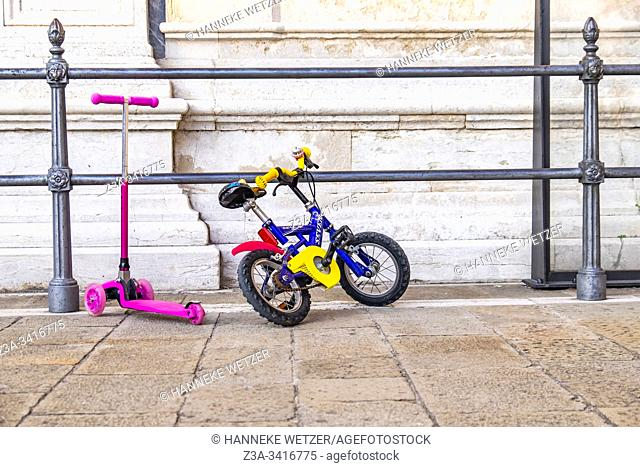 Kids bike and scooter parked against a fence in Venice, Italy