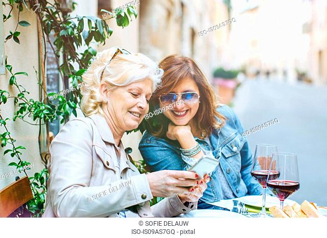 Two mature female friends looking at smartphone at sidewalk cafe, Tuscany, Italy