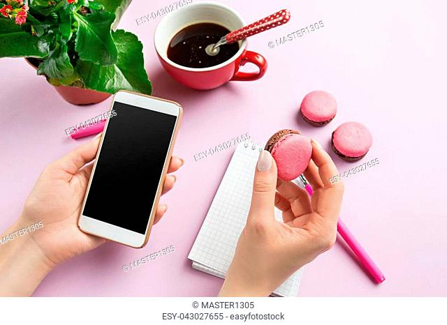 Female hands holding phone. Top view on french macarons on trendy color pink desk. Woman and stilish workplace. Cup of coffee, phone, notebook